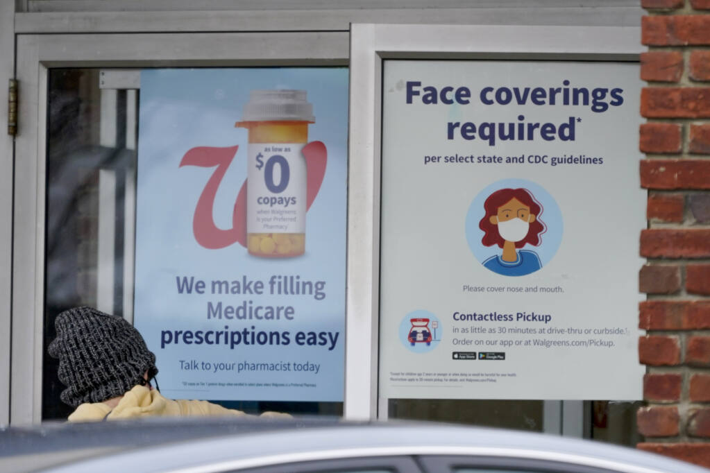 A patron opens the door with the signs requiring shoppers to comply with state COVID-19 guidelines to enter the Walgreens in Zelienople, Pa., Thursday, Jan. 28, 2021. (AP Photo/Keith Srakocic)