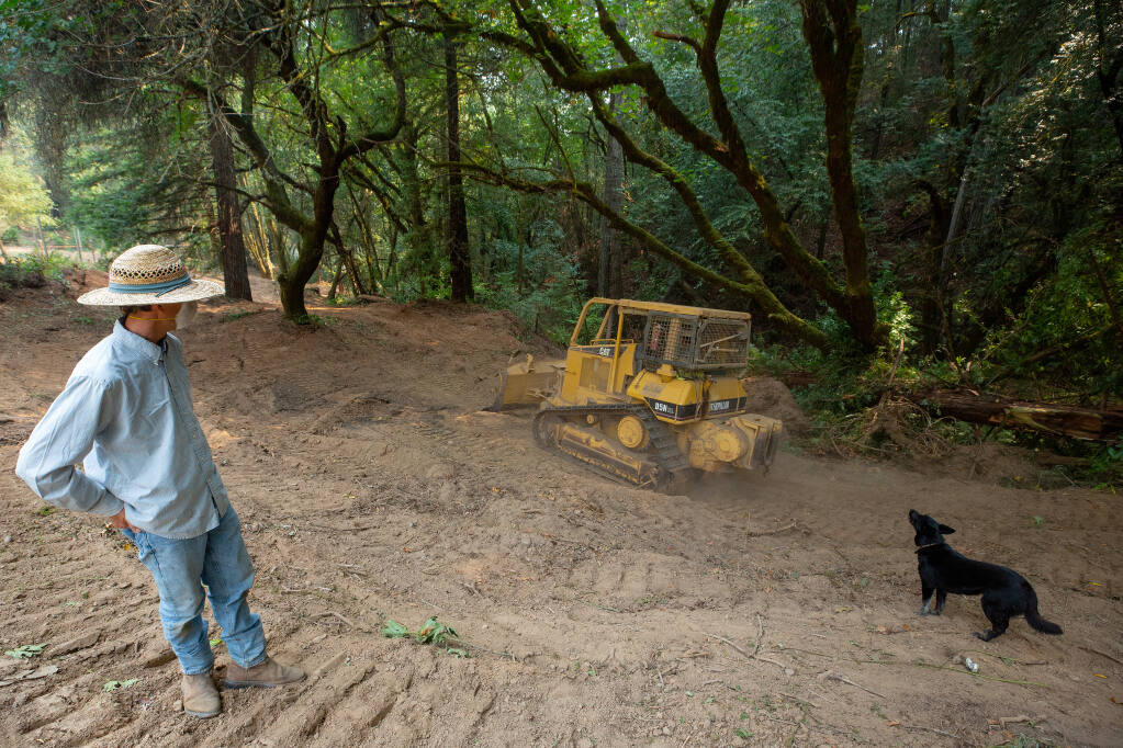 Nick Broderick and his dog, Blue, watch as a firefighting bulldozer rumbles back down a wide fire break, created with bulldozers to defend homes from the Walbridge fire, beside a tributary of Felta Creek in Healdsburg on Wednesday, Aug. 26, 2020. (Alvin A.H. Jornada / The Press Democrat)