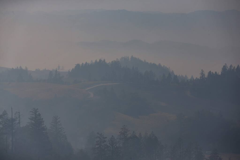 A thick haze of smoke engulfs the valley below Geysers Road, near Geyserville, on Friday, October 25, 2019. (Christopher Chung/ The Press Democrat)