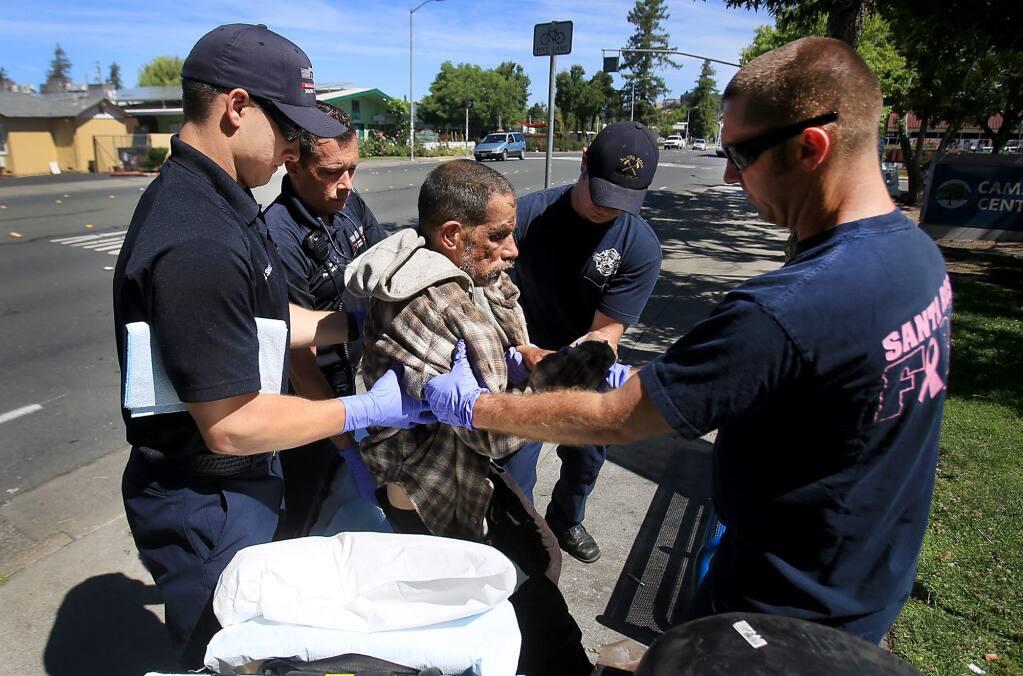 Santa Rosa firefighters assist homeless resident Teddy Lamantia on College Avenue near Santa Rosa Junior College, Tuesday June 21, 2016. (Kent Porter / Press Democrat) 2016