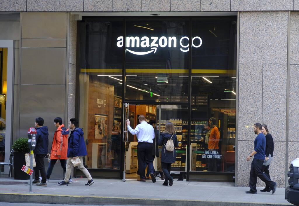 In this Wednesday, Jan. 30, 2019, photo people walk past and into an Amazon Go store in San Francisco. Get ready to say good riddance to the checkout line. A year after Amazon opened its first cashier-less store, startups and retailers are racing to get similar technology in other stores throughout the world, letting shoppers buy groceries without waiting in line. (AP Photo/Eric Risberg)