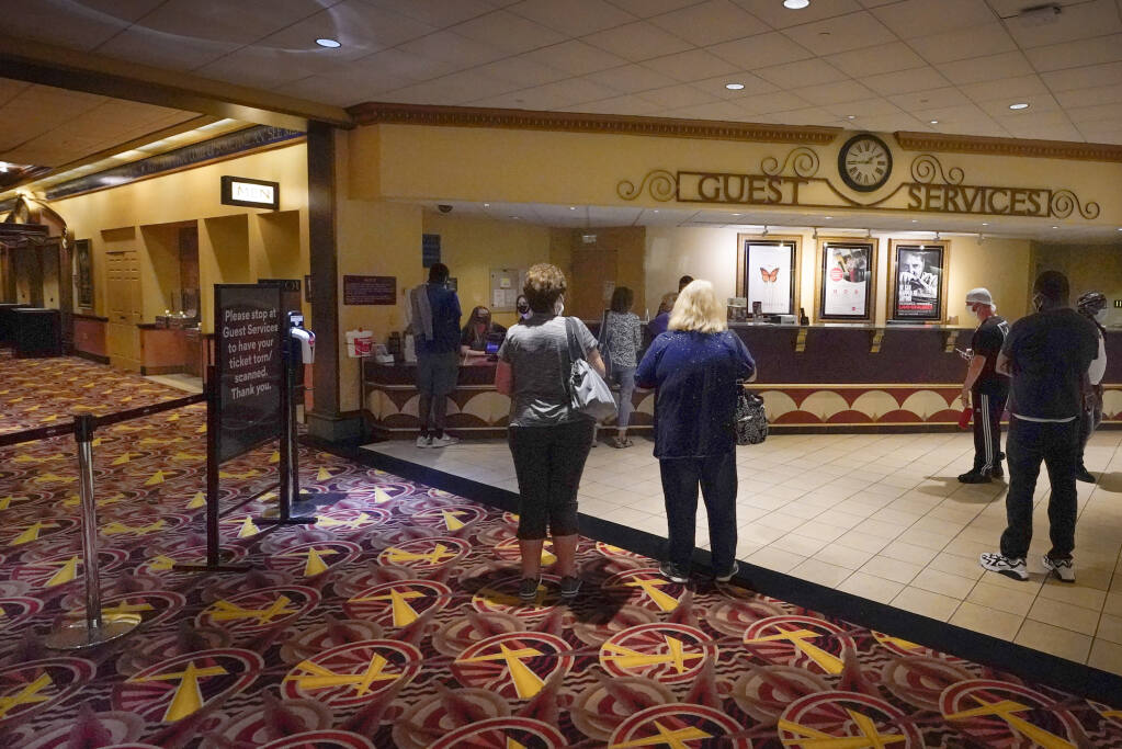 Patrons gather to get tickets for some of the first showings at the AMC theatre when it re-opened for the first time since shutting down at the start of the COVID-19 pandemic, Thursday, Aug. 20, 2020, in West Homestead, Pa. (AP Photo/Keith Srakocic)