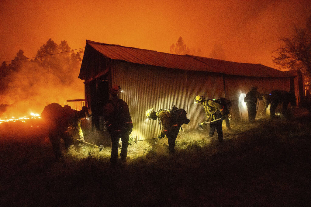 A hand crew clears vegetation from around a barn as the Bear Fire burns through the Berry Creek area of Butte County, Calif., on Wednesday, Sept. 9, 2020. The blaze, part of the lightning-sparked North Complex, expanded at a critical rate of spread as winds buffeted the region. (AP Photo/Noah Berger)
