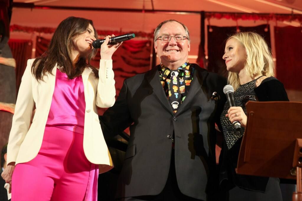 John Lasseter stands between Idina Menzel and Kristen Bell onstage during the Diane Disney Miller Lifetime Achievement Award ceremonies, at the Walt Disney Family Museum's 3rd Annual Fundraising Gala at the Golden Gate Club on November 7, 2017 in San Francisco, California. (Photo by Kelly Sullivan/Getty Images for The Walt Disney Family Museum)