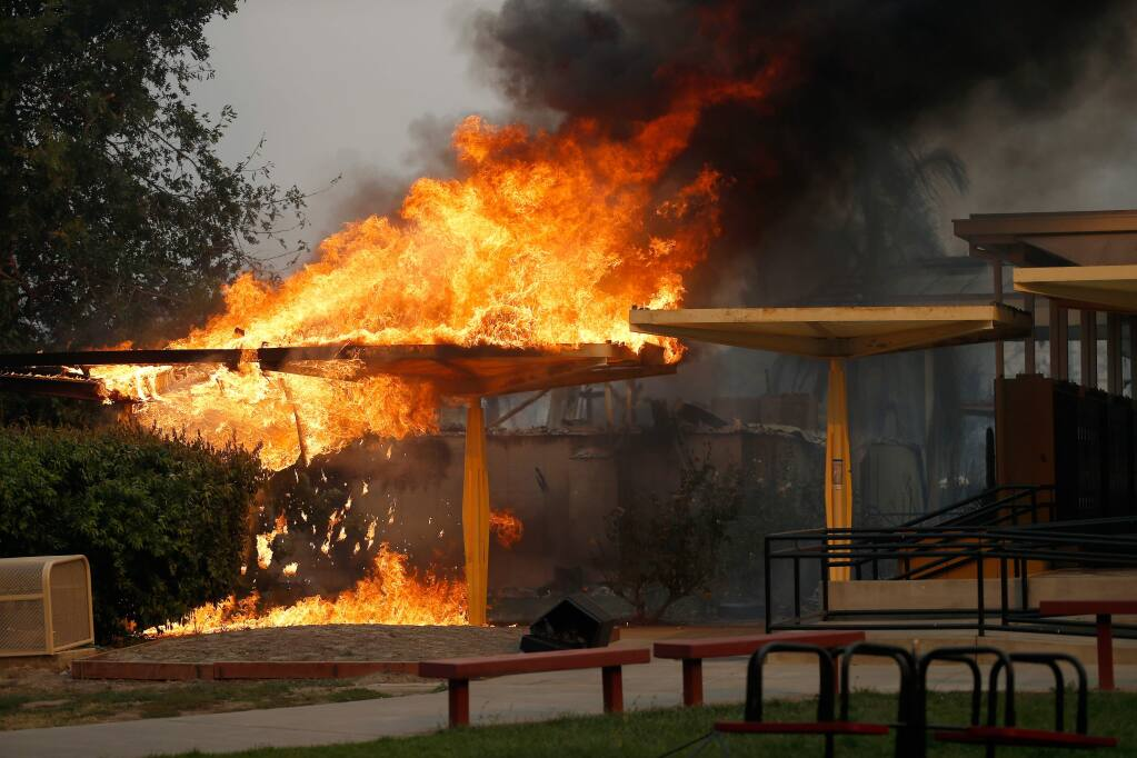 An awning blazes beside the locker area on the campus of Cardinal Newman High School after the Tubbs Fire burned through north Santa Rosa, California on Monday, Oct. 9, 2017. (ALVIN JORNADA/PD)