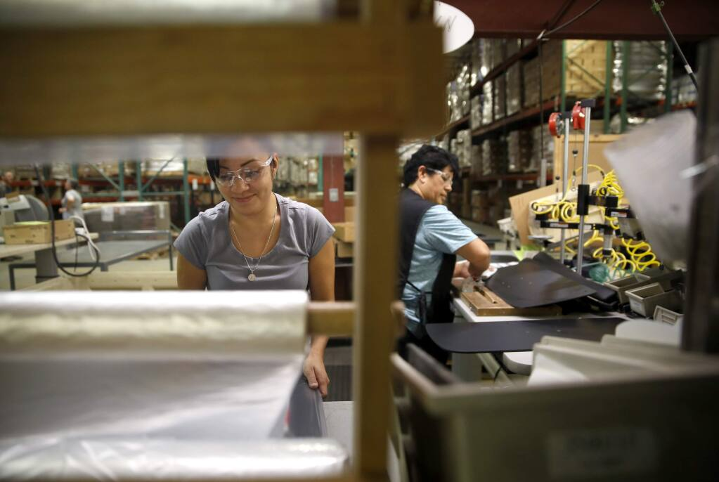 Cecilia Argos, left, and Christina Chavez assemble keyboard trays at Workrite Ergonomics on Tuesday, May 3, 2016 in Petaluma, California . (BETH SCHLANKER/ The Press Democrat)