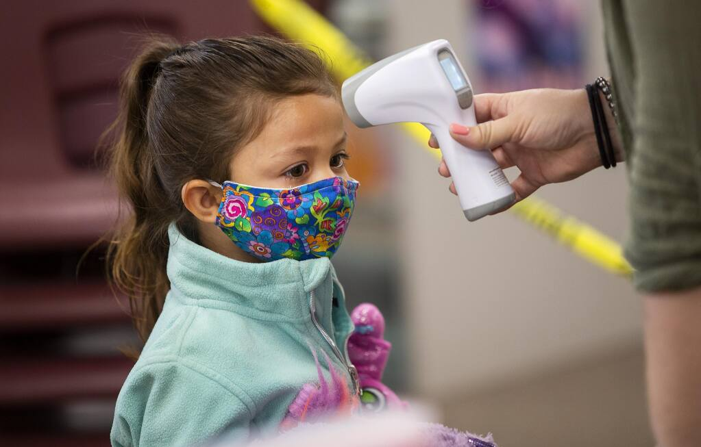 Kacey Menjivar, 4, has her temperature checked before the start of daycare at the North Bay Children's Center at Steele Lane School in Santa Rosa on Thursday, July 23, 2020.   (John Burgess/The Press Democrat)