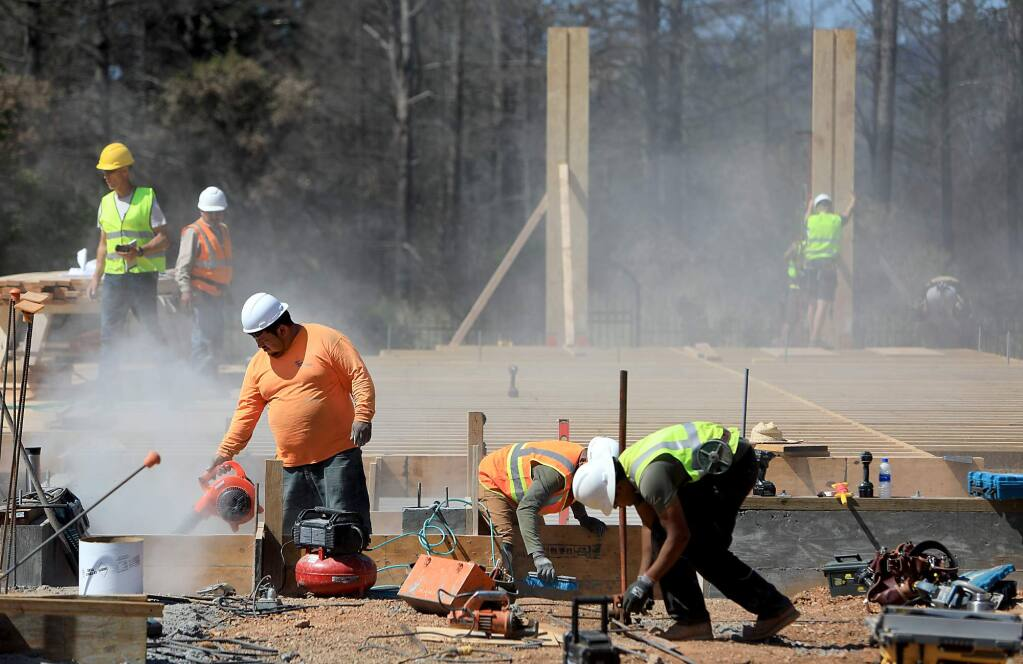 Construction workers build forms for a house in the Fir Ridge neighborhood of Fountaingrove, Monday, May 21, 2018, in Santa Rosa. The home was razed during the Tubbs fire. (Kent Porter / The Press Democrat) 2018