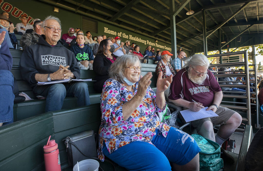 From left, die-hard fans Joe Gellura, Lisa Smith and Jack Chalmers keep score and root for their Prune Packers on the opening day of the baseball season in the 100th year of Healdsburg Recreation Park on Tuesday, June 8, 2021.  (Photo by John Burgess/The Press Democrat)