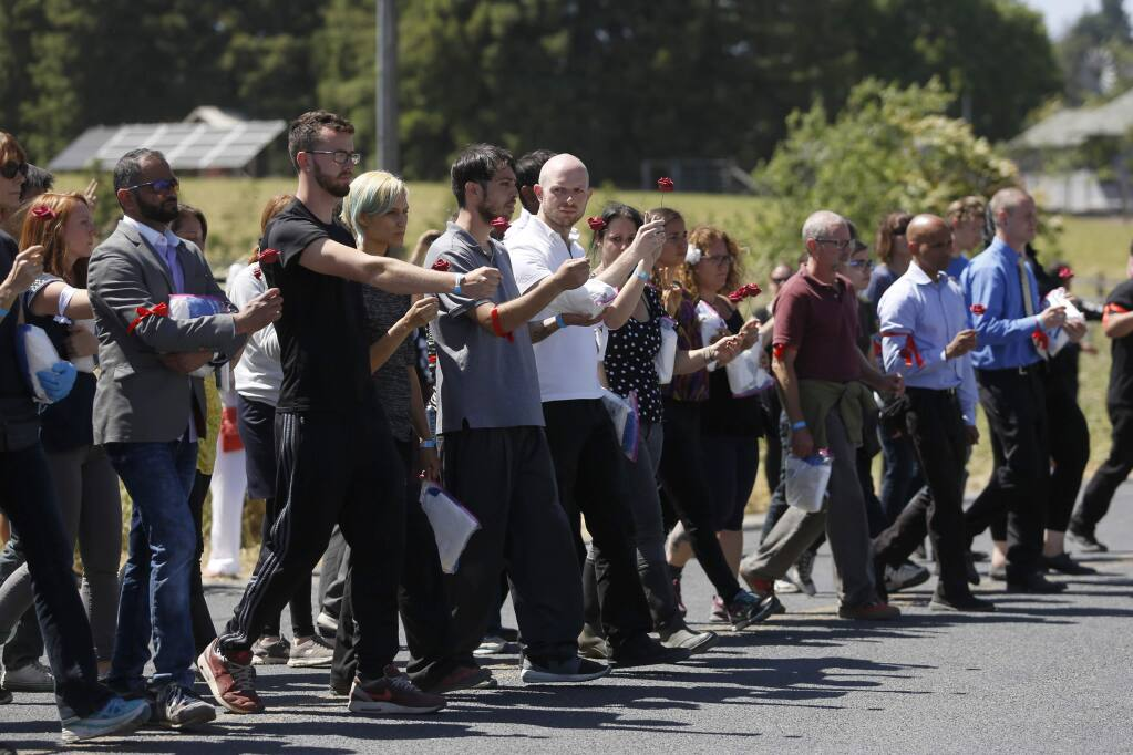 Protesters organized by Direct Action Everywhere, an animal rights network, approach a line of Sonoma County Sheriff's deputies in order to be arrested for trespassing at Weber Family Farms on Tuesday, May 29, 2018 in Petaluma, California . (BETH SCHLANKER/The Press Democrat)