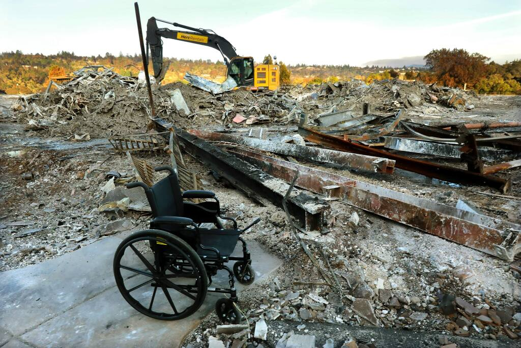 A wheelchair sits amidst the rubble of Villa Capri at Varenna, the assisted living and memory care unit in Fountaingrove, in this 2017 file photo. (John Burgess/The Press Democrat)