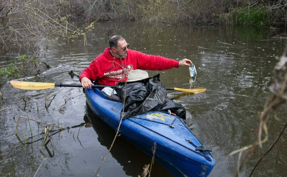 Bruce Cohn works to clean up the upper stretch of the Petaluma River by picking up trash as he kayaks on the high tide on Thursday morning March 7, 2013. Scott Manchester / The Press Democrat