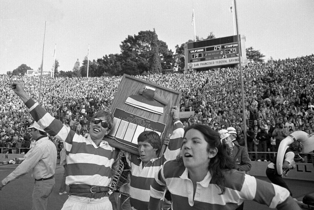 In this Nov. 20, 1982, file photo, the Stanford band goes wild on the field at the end of the Cal-Stanford game in Berkeley, thinking they had won, as the scoreboard says 20-19 with no time left. Known simply as The Play, Cal used five laterals and had to run over a Stanford trombone player to score the winning touchdown on the last play of the game in 1982. Stanford still does not acknowledge the victory and insists the play was illegal. (AP Photo/Carl Viti, File)
