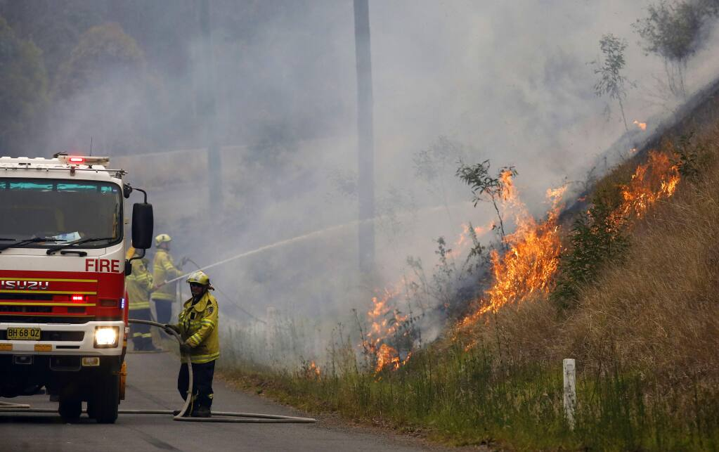 In Monday, Nov. 11, 2019, photo, firefighters work on a controlled burn in Koorainghat, New South Wales state, Australia. Hundreds of schools remained closed across Australia's most populous state on Tuesday, Nov. 12, and residents were urged to evacuate woodlands for the relative safety of city centers as authorities braced for extreme fire danger. (Darren Pateman/AAP Images via AP)