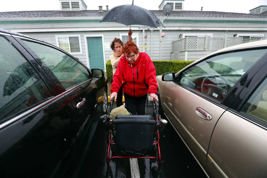 Volunteer Ginger Inglis holds an umbrella for Eleanor Jaquish, 84, as she picks her up from her Petaluma home to take her to her swim exercise class on Friday, February 17, 2017. (John Burgess/The Press Democrat)