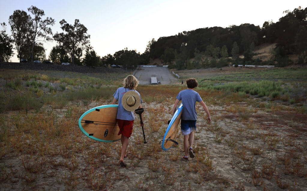 After a late afternoon of paddle boarding, Ukiah residents Zach Kmeall, 17, and Jacob Mello, 18, walk 250 yards from the shoreline (on the dredged boat ramp) to their vehicles, Thursday, July 15, 2021 at Lake Mendocino east of Ukiah.    (Kent Porter / The Press Democrat)