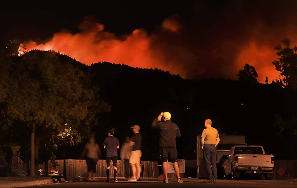 Waken in the dead of night on an order to evacuate, Skyhawk residents watch the glow of an approaching fire from their Skyhawk Homes near Los Alamos Road in Santa Rosa, Saturday Oct. 14, 2017. They eventually left the area. (Kent Porter / The Press Democrat) 2017
