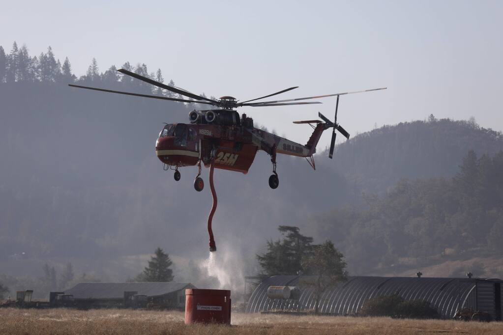 A helicopter fills up with fire retardant from a tank off Franz Valley Road in Healdsburg on Wednesday, Oct. 30, 2019. (BETH SCHLANKER/ PD)