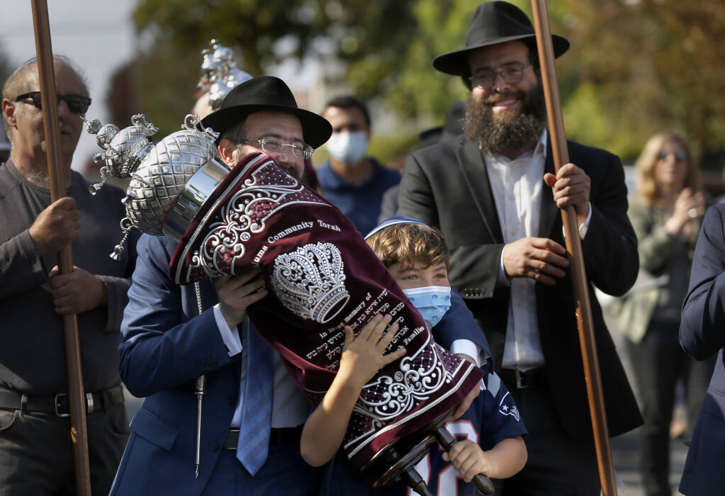 Rabbi Dovid Bush and Simon Goldstein, 8,  carry a newly finished Torah scroll in a procession from Penry Park to the Chabad Jewish Center in Petaluma on Sunday, Aug. 22, 2021. (BETH SCHLANKER/THE PRESS DEMOCRAT)