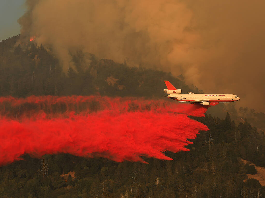 Natural disasters such as 2020's Glass Fire, which damaged or destroyed over two dozen wineries in Napa and Sonoma counties are a key driver in the expected rise of commercial property policy rates by an average of 13.6% this year. In this photo, a QA DC-10 drops retardant on the west slope of Mt. St. Helena during the Glass Fire on Sept. 30, 2020. (Kent Porter / The Press Democrat)