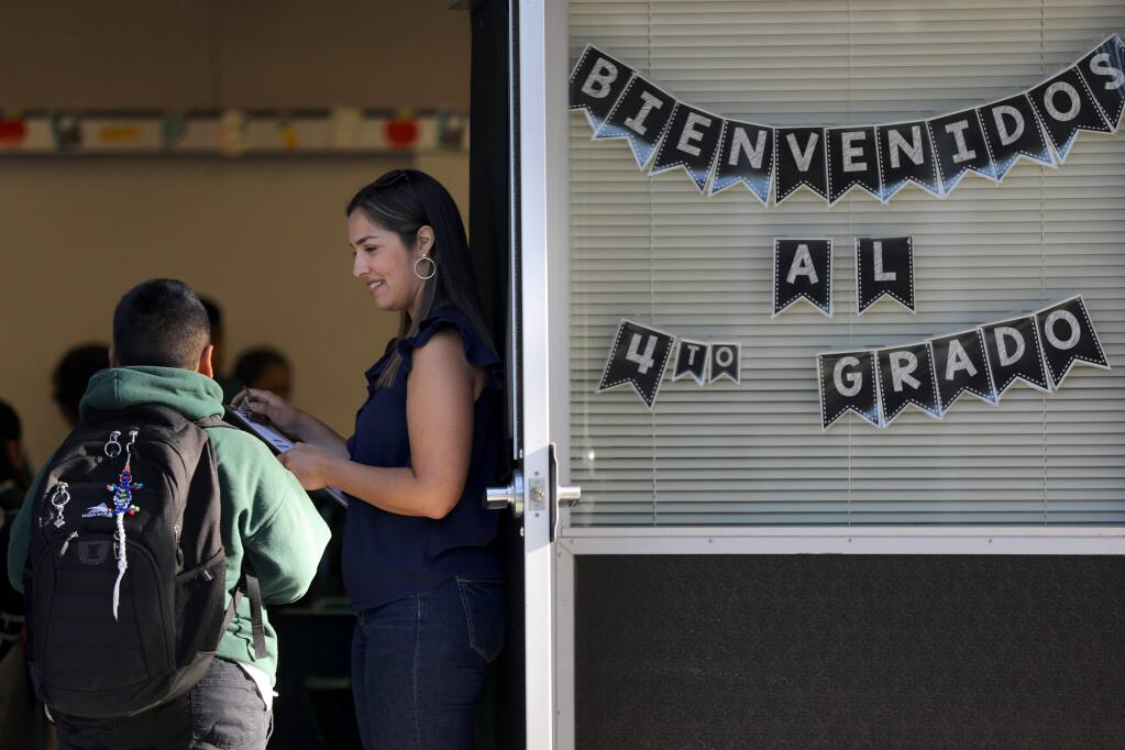 Fourth-grade teacher Raquel Figueroa welcomes students during the first day of class at Cesar Chavez Language Academy on the Lawrence Cook Middle School campus in Santa Rosa on Wednesday, Aug. 14, 2019. (Beth Schlanker / The Press Democrat)