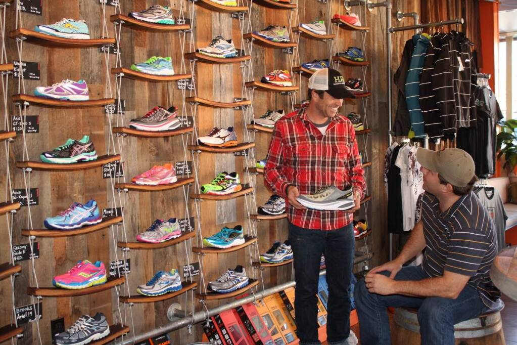 PHOTO: 1 by ANN CARRANZA-Owner Skip Brand shows a shoe to a client at Healdsburg Running Company.