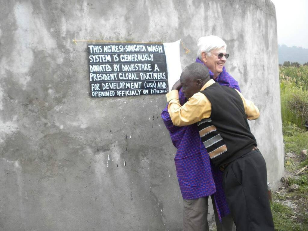 PHOTO: 1 by LEE STARE -Retired vintner Dave Stare poses with a grateful east African resident next to a water tank set up by Global Partners as part of its Songota WASH project in rural Ng'iresi outside of Arusha, Tanzania. Stare is president of the board for the Rohnert Park-based nonprofit agency.