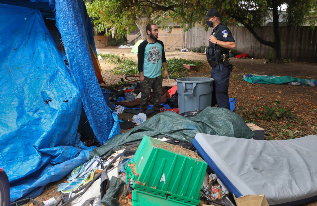 Santa Rosa Police Officer Ryan Cadaret, right, talks to James Hover about moving his encampment at Fremont Park in Santa Rosa on Wednesday, July 29, 2020. Homeless encampments were moved from the western area of the park to mitigate fire risk. (Christopher Chung / The Press Democrat)