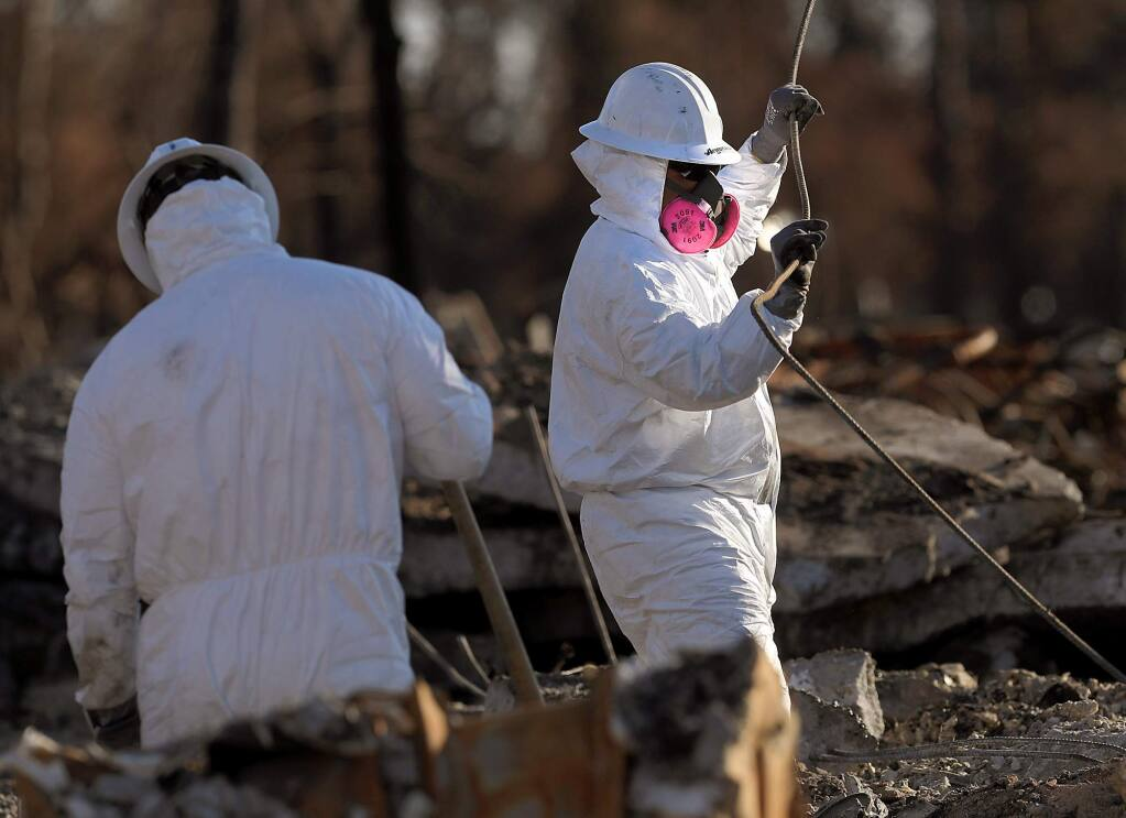 A crew from Argonaut Constructors of Santa Rosa work to clear debris from a razed home on Hillary Court in Coffey Park, Monday Nov. 6, 2017, one month after the Tubbs fire roared through Santa Rosa. (Kent Porter / The Press Democrat) 2017