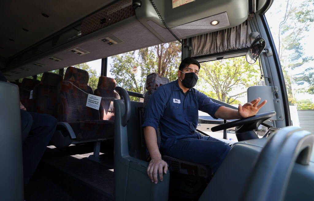Diesel technician Manny Nunez moves an Airport Express bus into position to be inspected in Santa Rosa on Thursday, April 29, 2021.  (Christopher Chung/ The Press Democrat)