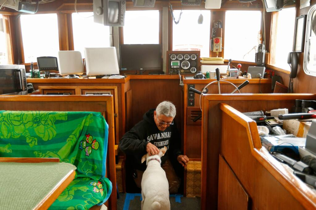 Crab fisherman Dick Ogg is greeted by his dog Buster as he emerges from the engine room of his boat the Karen Jeanne at Spud Point Marina in Bodega Bay, California, on Saturday, November 26, 2016. North Coast fishermen brace for another tough year after state officials announced another delay to commercial crab fishing off the Sonoma and Mendocino County coasts. (Alvin Jornada / The Press Democrat)