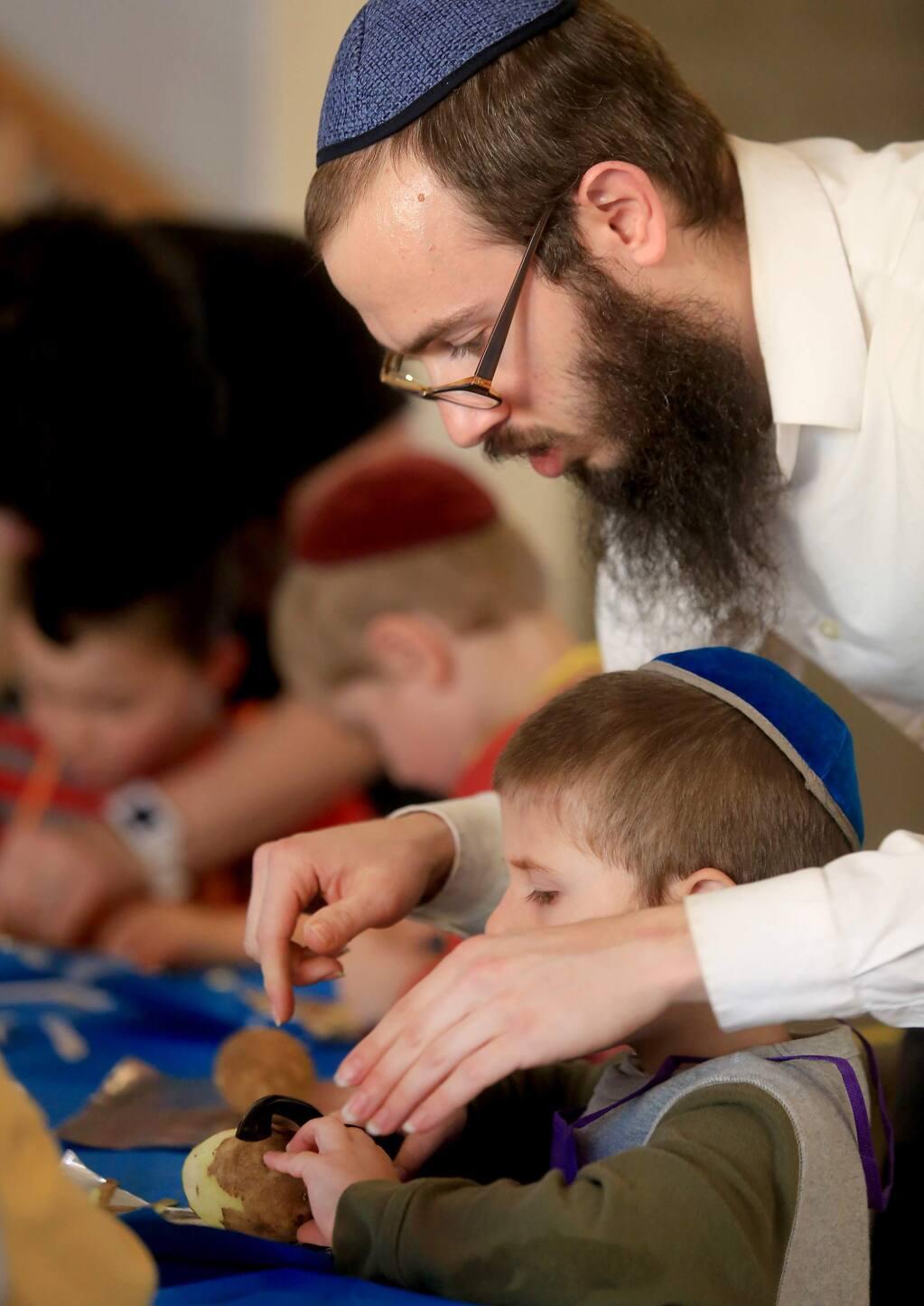 Rabbi Dovid Bush helps his son Shlomie make Boureka, thin Jewish pastries, at their home in Petaluma, as part of the Kids in the Kitchen program run by Dovid's wife, Devorah Bush.Kent Porter Press Democrat