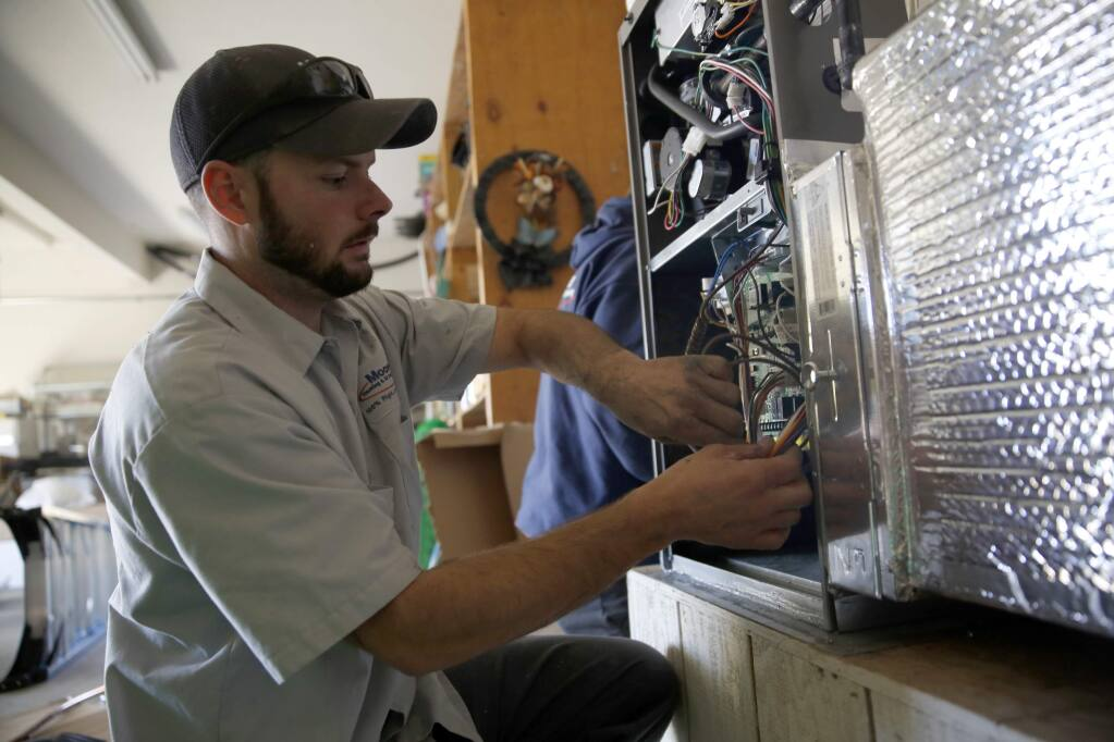 Micah Pierce, a technician with Moore Heating and Air Conditioning, installs a new furnace at a home on Wednesday, December 31, 2014 in Graton, California . (BETH SCHLANKER/ The Press Democrat)