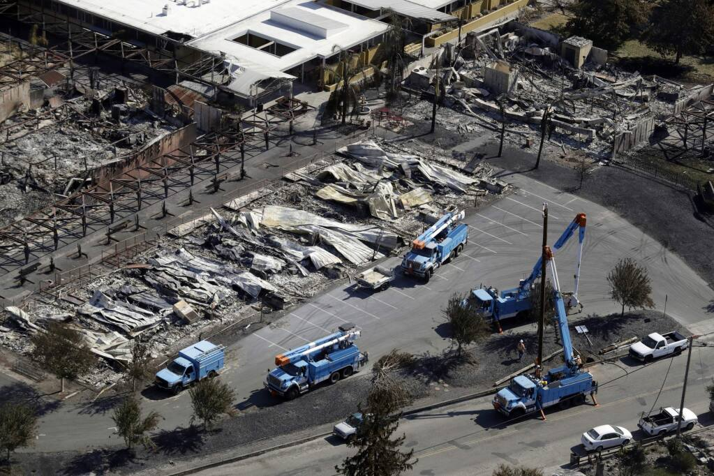 FILE - In this Oct. 14, 2017, file photo, Pacific Gas & Electric crews work on restoring power lines in a fire-ravaged neighborhood in an aerial view in the aftermath of a wildfire in Santa Rosa, Calif. (AP Photo/Marcio Jose Sanchez, File)