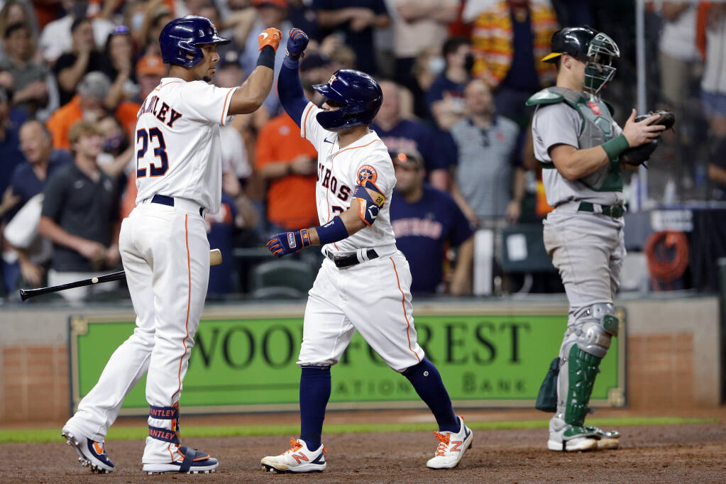 The Houston Astros' Michael Brantley; left, and Jose Altuve high-five next to Oakland Athletics catcher Sean Murphy, right, after Altuve's home run during the seventh inning on Thursday, April 8, 2021, in Houston. (Michael Wyke / ASSOCIATED PRESS)