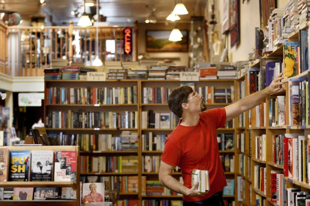 Aaron Rosewater, co-owner of Levin & Company, organizes the shelves at his bookstore in Healdsburg on Tuesday, August 21, 2018. (Beth Schlanker/ The Press Democrat)