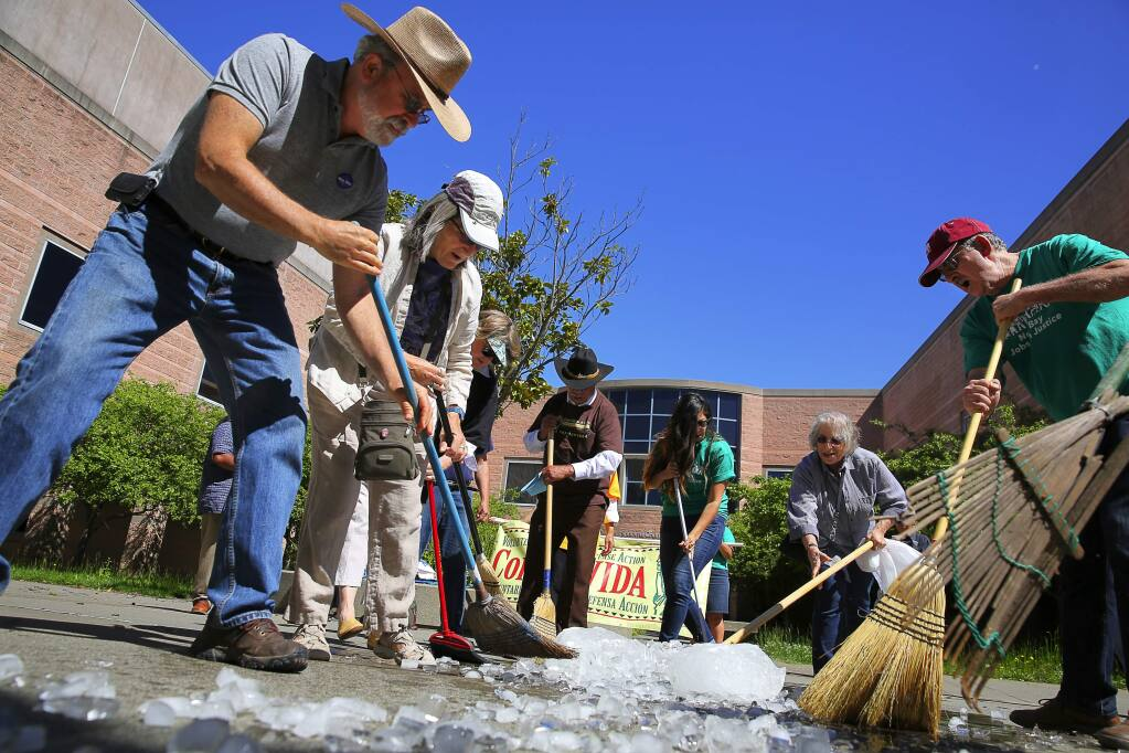 Terry Winter, left, Vicki Smith, Liz Finn, second from right, and Marty Bennett sweep away ice, at the Sonoma County Adult Detention Facility, in a demonstration to protest the Sonoma County Sheriff's Office sharing of information of undocumented inmates with the U.S. Immigration and Customs Enforcement, in Santa Rosa on Monday, May 1, 2017. (Christopher Chung/ The Press Democrat)