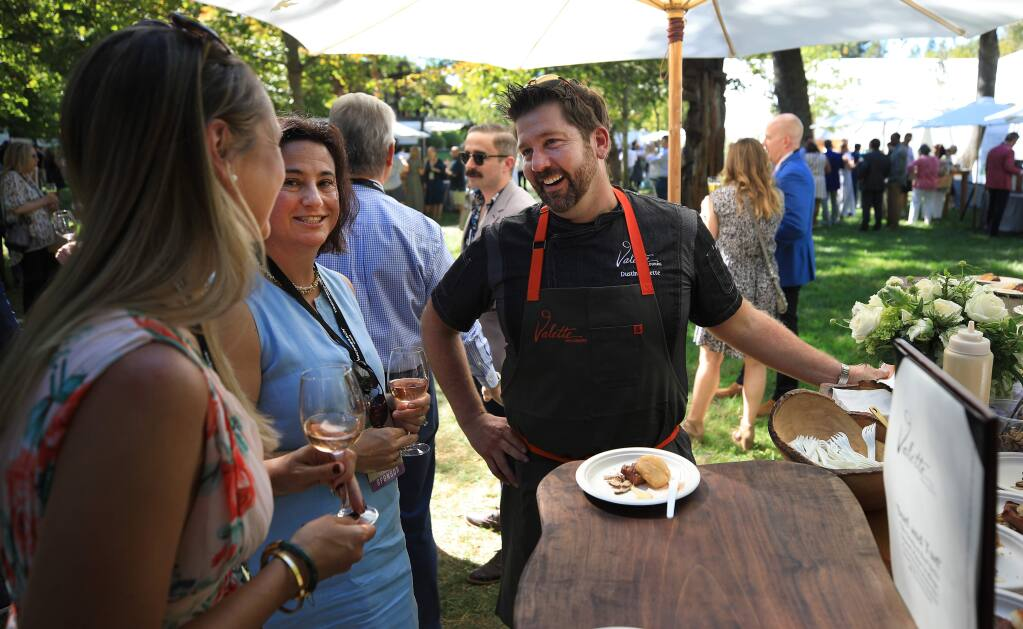 Restaurant owner Dustin Valette greets friends prior to the Sonoma County Wine Auction at La Crema Estate at Saralee's Vineyard in Windsor, Saturday, Sept. 21, 2019. (Kent Porter / The Press Democrat