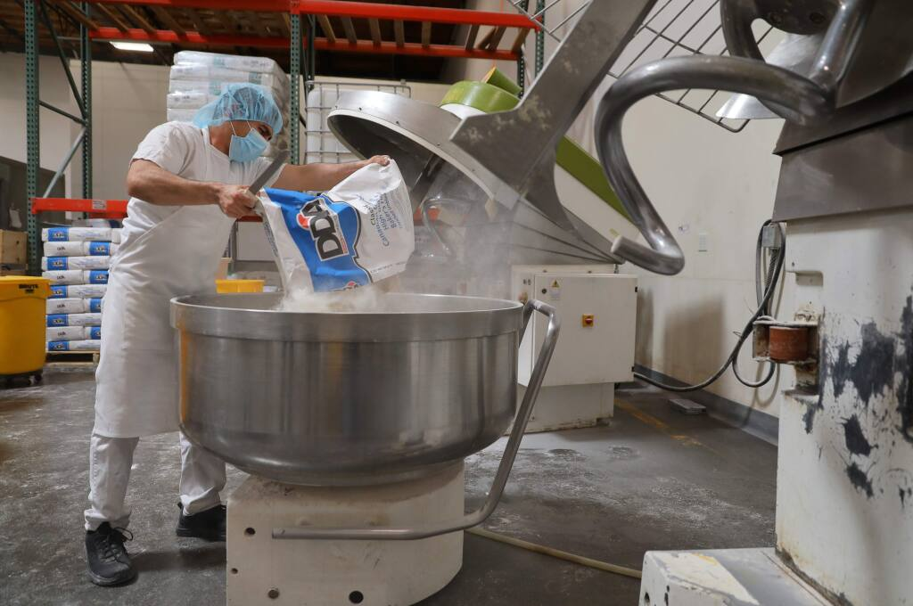 Felipe Carrillo pours a bag of flour into large mixing bowl while making sourdough bread at the Costeaux French Bakery production facility in Santa Rosa on Wednesday, April 15, 2020. (Christopher Chung/ The Press Democrat)