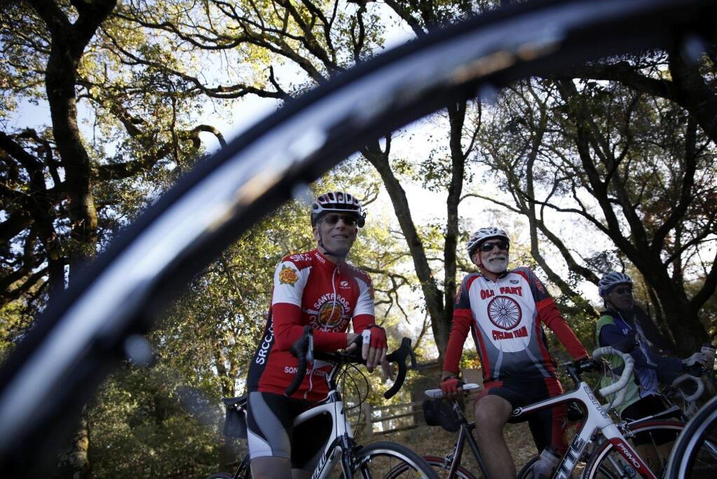 Cyclists Bob Owen, left, and Frankie Sottile meet up with members of the Santa Rosa Cycling Club at Howarth Park before the start of their ride in Santa Rosa on Wednesday, Oct. 2, 2013. (BETH SCHLANKER / The Press Democrat)