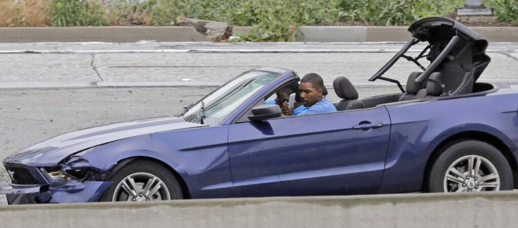 The driver of a convertible blue Mustang holds a personal device and looks into his side-view mirror as he speeds down the busy Harbor Freeway (Interstate 110) in downtown Los Angeles, as he and a passenger are pursued in a chase on rainy Southern California streets and highways, Thursday, April 7, 2016. Authorities arrested the two burglary suspects after they stopped the car in a South Los Angeles neighborhood, exchanged high-fives with onlookers and took selfies before officers arrived several minutes later and handcuffed them. (AP Photo/Reed Saxon)