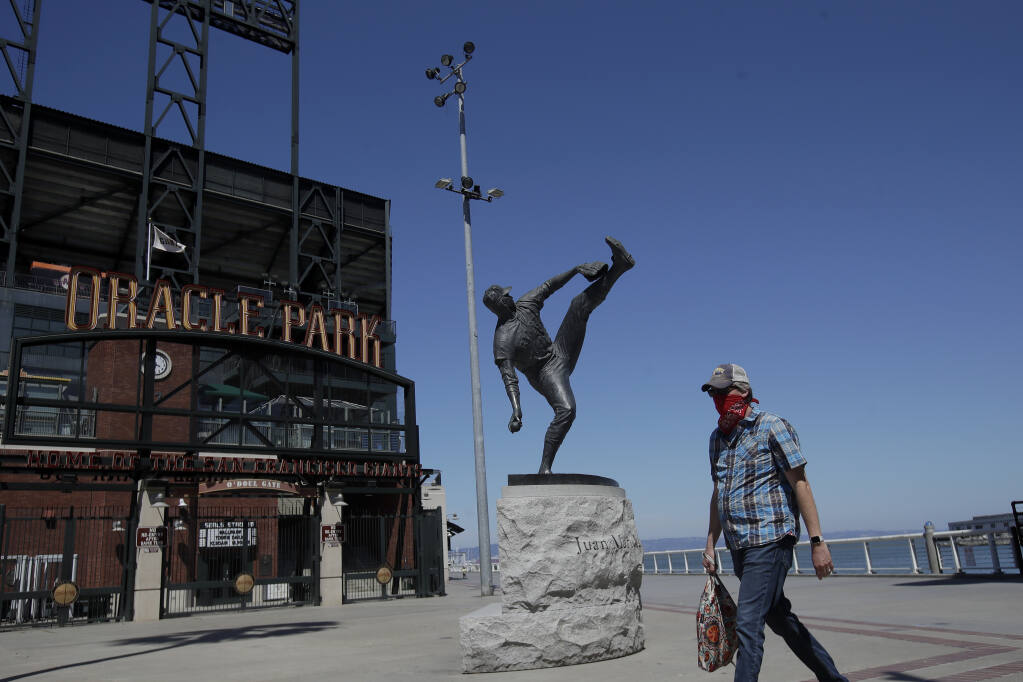 A man wearing a mask walks by the statue of Hall of Fame pitcher Juan Marichal outside of the Giants' Oracle Park in San Francisco, Thursday, June 25, 2020. (Jeff Chiu / ASSOCIATED PRESS)
