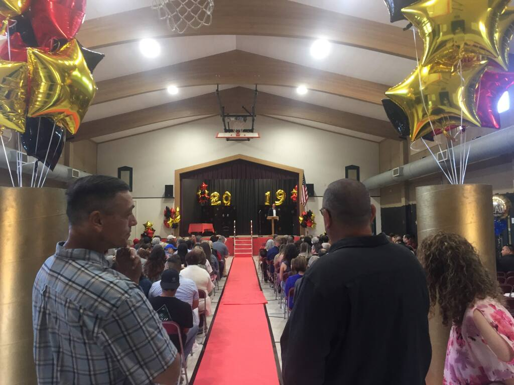 David Stephens, left, stands before the sixth grade promotion ceremony at San Miguel Elementary School that he helped set up Friday, May 31, 2019. (Maci Martell/for The Press Democrat)