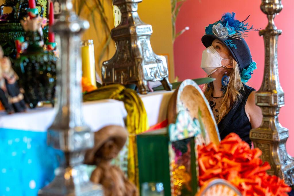 Annaliese Quisisem takes in the details of the public ofrenda displayed at the Dia de los Muertos exhibit at the Petaluma Arts Center in Petaluma on Saturday, Oct. 31, 2020. (ALVIN JORNADA/THE PRESS DEMOCRAT)
