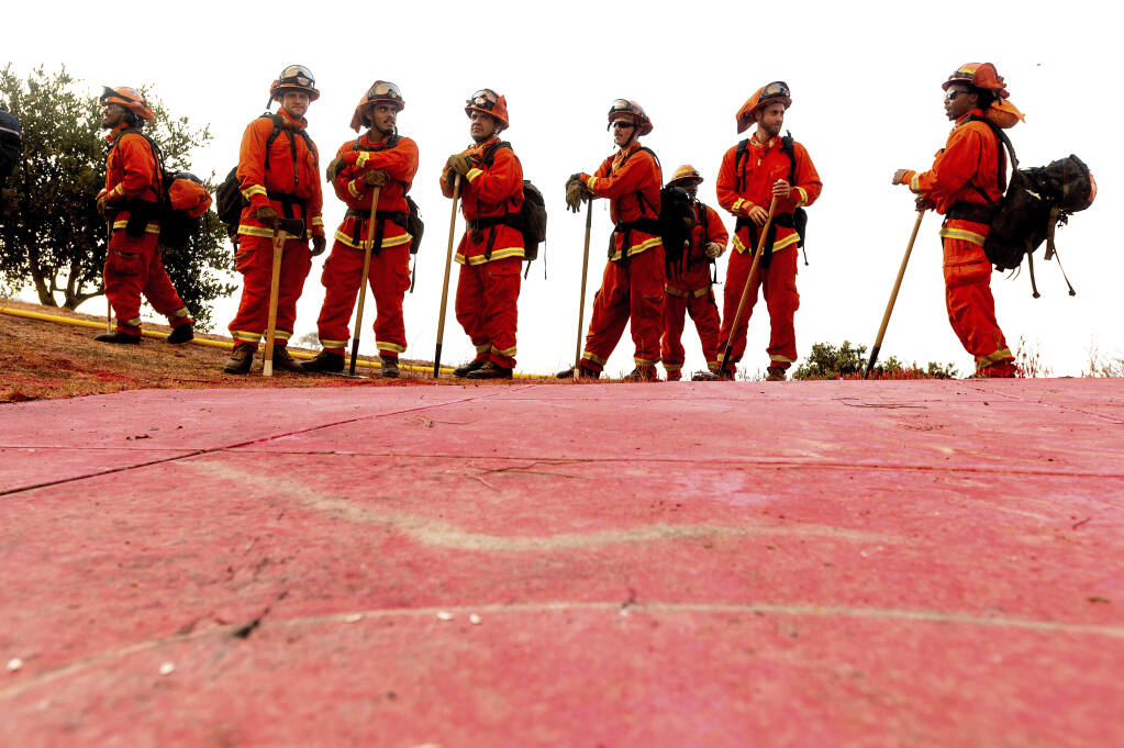 """FILE - In this Aug. 17, 2020, file photo, inmate firefighters - notable by their bright orange fire gear compared to the yellow worn by professional firefighters - prepare to take on the River Fire in Salinas, Calif. California could change its constitutional ban on slavery to remove the words """"unless for the punishment of crime,"""" further reducing the state's already faltering dependence on thousands of inmate firefighters, under a proposed amendment backed Thursday, Feb. 25, 2021, by local officials and actor-activist Danny Glover. (AP Photo/Noah Berger, File)"""