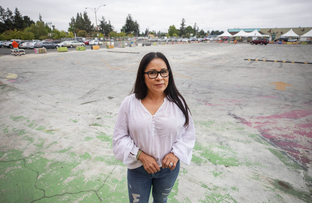Sylvia Camacho stands in the proposed site of a proposed 175-unit housing development in the middle of the present Roseland Village Shopping Center. Camacho welcomes new customers but fears the development will leave her old customers without a place to park. (John Burgess / The Press Democrat)