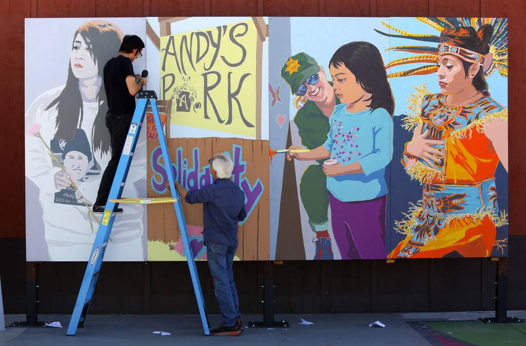 Artists Daniel Doughty and Mario Uribe hang a multi-panel Healing Mural they created honoring the memory of Andy Lopez at the Roseland Village Neighborhood Center on Thursday in preparation for the unveiling on Friday. (John Burgess/The Press Democrat)