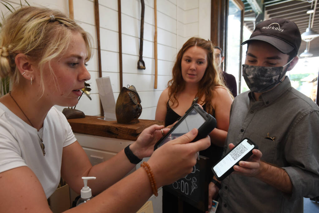 Fern Bar hostess Michaela Codding, left, scans a QR code to verify COVID-19 vaccinations of guests Michael Estems, 26, right, and Katie-Lauren Dunbar, 26, both from Santa Rosa, on Wednesday, July 28, 2021, in Sebastopol. (Erik Castro / For The Press Democrat)