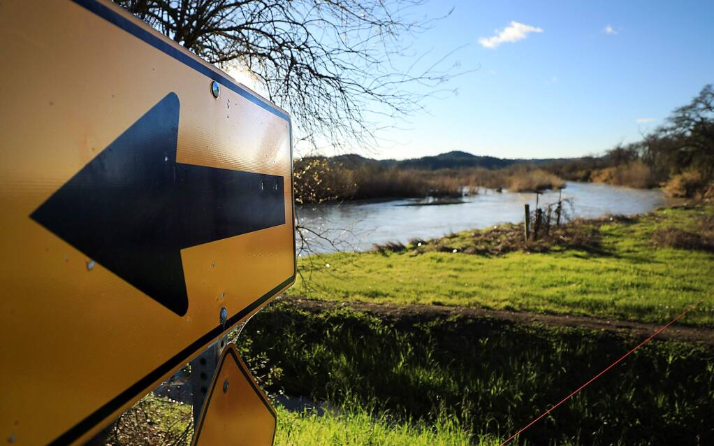 A sign points to a bend in River Road as the Russian River eats away at the east side of the river bank at River Road in Geyserville, Tuesday, Feb. 5, 2019, putting the roadway at risk for collapse. (Kent Porter / The Press Democrat) 2019