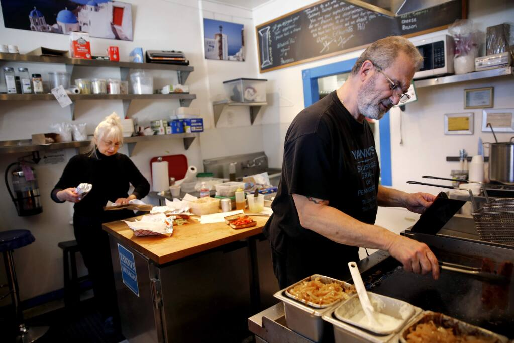 John and Francesca Vrattos work to fill lunch orders during the last day of business Sunday at Yanni's Sausage Grill, Feb. 25, 2018 in Penngrove, California. (BETH SCHLANKER/The Press Democrat)
